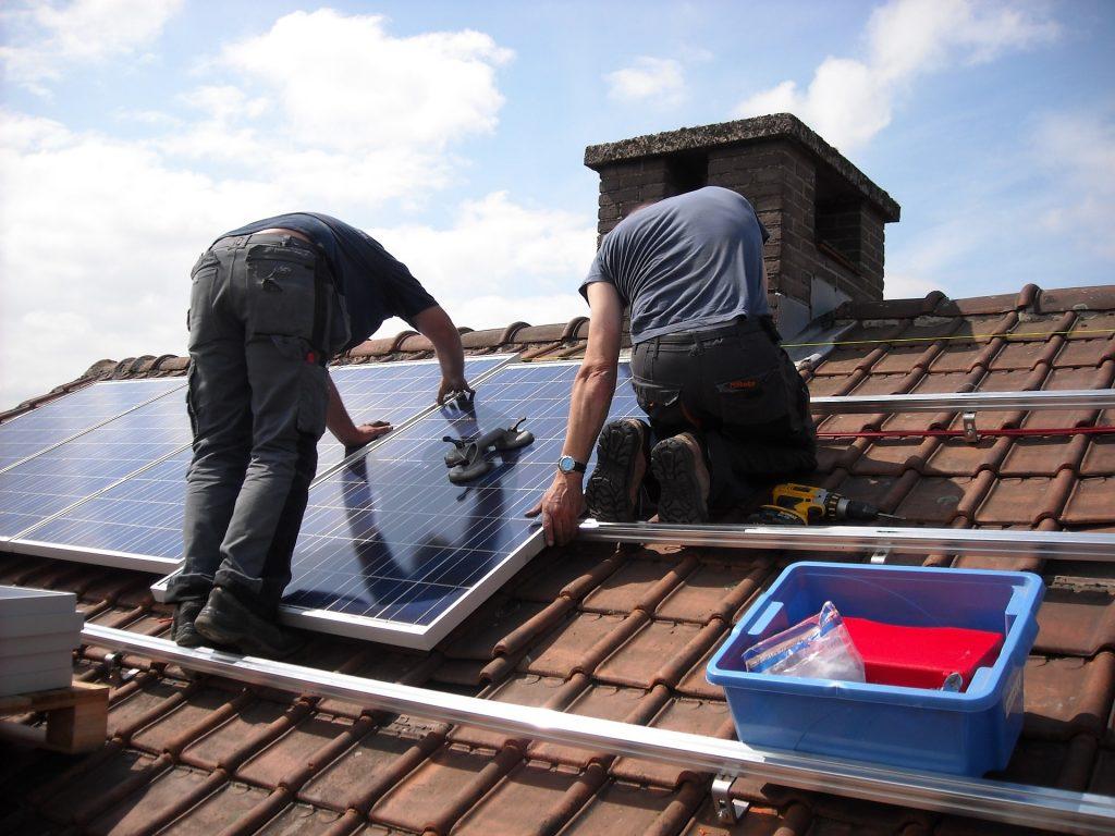 Dos técnicos instalan paneles de energía solar en una casa.