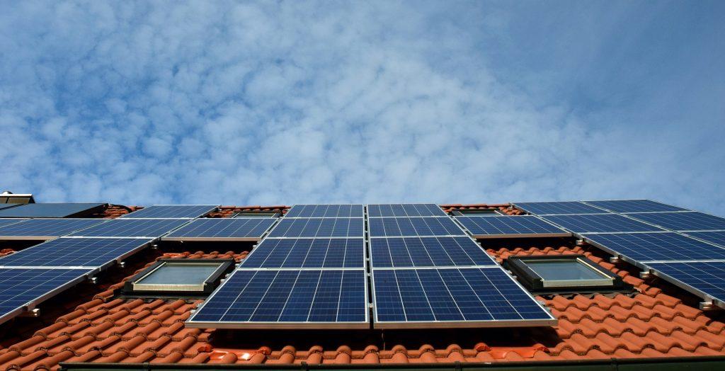 Un edificio de viviendas con un sistema de paneles solares de autoconsumo en el tejado.